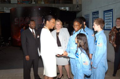KENNEDY SPACE CENTER, FLA. - At the Museum of Science and Industry (MOSI) in Tampa, Dr. Adena Williams Loston, chief education officer at NASA Headquarters, greets students from one of NASA?s Explorer Schools, Stewart Middle School in Tampa. The students as well as Dr. Loston and KSC Deputy Director Dr. Woodrow Whitlow Jr. (far left) were at MOSI to view the space exhibits Space: A Journey to Our Future, an extraordinary, interactive exhibition designed to entertain, educate and inspire; and SPACE STATION, the first cinematic journey to the International Space Station (ISS), where audiences can experience for themselves life in zero gravity aboard the new station.