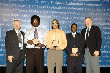 KENNEDY SPACE CENTER, FLA. - At the ?1st Space Exploration Conference: Continuing the Voyage of Discovery,? being held at Disney?s Contemporary Resort in Orlando, the NASA Explorer School team from McNair High School in Dekalb County, Ga., receives the Space Exploration Video Festival award sponsored by Lockheed Martin. Standing with the awards are Trenten Nash, Theo Maxie and Daniel Jackson. Presenting the awards were John Karas (left), with Lockheed, and Adm. Craig Steidle (right), associate administrator, Office of Exploration Systems at NASA. The three-day conference drew attendees from around the world. It presented topics on new missions, technologies and infrastructure needed to turn the vision for space exploration into reality. Keynote speakers at the three-day conference include NASA Administrator Sean O'Keefe, Congressman Dave Weldon, film director James Cameron and NASA?s senior Mars scientist James Garvin. The conference has drawn attendees from around the world.