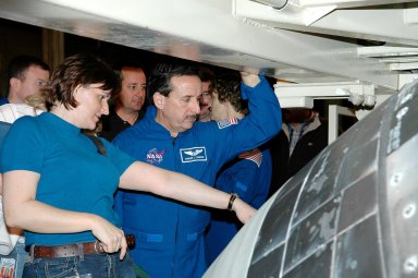 KENNEDY SPACE CENTER, FLA. - In the Orbiter Processing Facility, STS-114 Mission Specialist Charles Camarda looks closely at the tiles on Discovery. At left is Cindy Begley, lead EVA flight controller. The tiles are part of the Thermal Protection System on the orbiter. Behind Camarda are Pilot James Kelly (far left) and Commander Eileen Collins (right). They and other crew members are at KSC for Crew Equipment Interface Test activities. During CEIT, the crew has an opportunity to get a hands-on look at the orbiter and equipment they will be working with on the mission. Return to Flight Mission STS-114 will carry the Multi-Purpose Logistics Module Raffaello, filled with supplies for the International Space Station, and a replacement Control Moment Gyroscope. Launch of STS-114 has a launch window of May 12 to June 3.