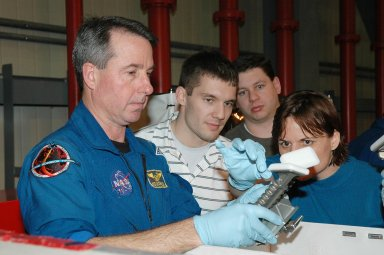 KENNEDY SPACE CENTER, FLA. - In the Orbiter Processing Facility, Mission Specialist Stephen Robinson (left) examines a tool from the Tool Stowage Assembly. He and other crew members are at Kennedy for Crew Equipment Interface Test activities. During CEIT, the crew has an opportunity to get a hands-on look at the payloads with which they?ll be working on orbit. The Return to Flight mission STS-114 will carry a replacement Control Moment Gyroscope and the Multi-Purpose Logistics Module Raffaello, filled with supplies for the International Space Station. Launch of STS-114 has a launch window of May 12 to June 3.