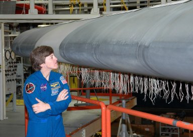 KENNEDY SPACE CENTER, FLA. - In the Orbiter Processing Facility, STS-114 Mission Specialist Wendy Lawrence looks closely at Discovery?s wing leading edge. The leading edge panels of the orbiters? wings have 22 Reinforced Carbon-Carbon panels, made entirely of carbon composite material. The molded components are approximately 0.25-inch to 0.5-inch thick. Lawrence and other crew members are at KSC for Crew Equipment Interface Test activities. During CEIT, the crew has an opportunity to get a hands-on look at the orbiter and equipment they will be working with on the mission. Return to Flight Mission STS-114 will carry the Multi-Purpose Logistics Module Raffaello, filled with supplies for the International Space Station, and a replacement Control Moment Gyroscope. Launch of STS-114 has a launch window of May 12 to June 3.