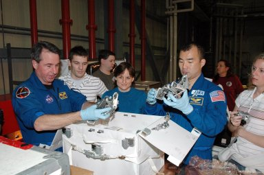 KENNEDY SPACE CENTER, FLA. - In the Orbiter Processing Facility, members of the STS-114 crew look at tools from the Tool Stowage Assembly. At left is Mission Specialist Stephen Robinson; at right is Mission Specialist Soichi Noguchi, who is with the Japanese Space Agency. They and other crew members are at Kennedy for Crew Equipment Interface Test activities. During CEIT, the crew has an opportunity to get a hands-on look at the payloads with which they?ll be working on orbit. The Return to Flight mission STS-114 will carry a replacement Control Moment Gyroscope and the Multi-Purpose Logistics Module Raffaello, filled with supplies for the International Space Station. Launch of STS-114 has a launch window of May 12 to June 3.