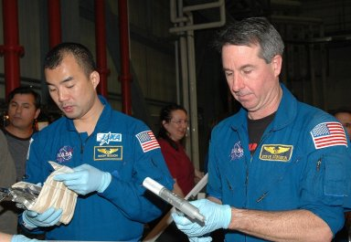 KENNEDY SPACE CENTER, FLA. - In the Orbiter Processing Facility, STS-114 Mission Specialists Soichi Noguchi (left) and Stephen Robinson look at tools from the Tool Stowage Assembly. Robinson is holding the External Tank/umbilical door tool (one that is used if, during an EVA, an astronaut would have to manually close the ET Umbilical doors). The crew is at KSC for Crew Equipment Interface Test activities. During CEIT, the crew has an opportunity to get a hands-on look at the payloads with which they?ll be working on orbit. The Return to Flight mission STS-114 will carry a replacement Control Moment Gyroscope and the Multi-Purpose Logistics Module Raffaello, filled with supplies for the International Space Station. Launch of STS-114 has a launch window of May 12 to June 3.