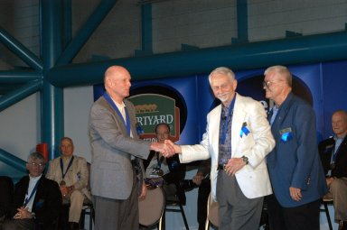 KENNEDY SPACE CENTER, FLA. - At the Astronaut Hall of Fame Induction Ceremony, new inductee Gordon Fullerton (left) is congratulated by Chairman Owen Garriott. At right is Hall of Famer Fred Haise. Other Hall of Famers are gathered on stage for the ceremony, which is being held in the Kennedy Space Center Visitor Complex?s Apollo/Saturn V Center. Recognized for their individual flight accomplishments and contributions to the success and future success of the U.S. space program, this elite group of inductees is among only 60 astronauts to be honored in the Hall of Fame and the fourth group of Space Shuttle astronauts named.