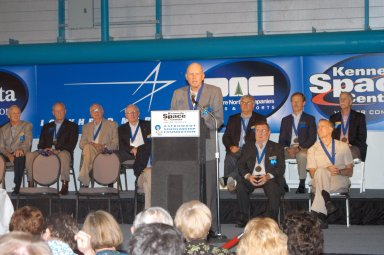 KENNEDY SPACE CENTER, FLA. - At the Astronaut Hall of Fame Induction Ceremony, new inductee Gordon Fullerton addresses guests. Behind him are current Hall of Famers (from left, back row) Al Worden, Charles Duke, Jack Lousma, Bill Pogue, Dan Brandenstein, Robert ?Hoot? Gibson and Stephen Covey; (in front row) Fred Haise and Vance Brand. The other new inductees are Bruce McCandless and Joe Allen. The event is being held in the Kennedy Space Center Visitor Complex?s Apollo/Saturn V Center. Recognized for their individual flight accomplishments and contributions to the success and future success of the U.S. space program, this elite group of inductees is among only 60 astronauts to be honored in the Hall of Fame and the fourth group of Space Shuttle astronauts named.