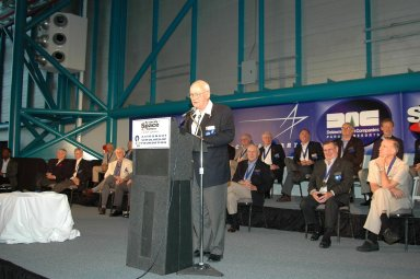 KENNEDY SPACE CENTER, FLA. - At the Astronaut Hall of Fame Induction Ceremony, new inductee Bruce McCandless speaks to the guests. Seen behind him are current Hall of Famers (back row) Al Gordon, Walt Cunningham, Jack Lousma, Bill Pogue, Robert Crippen, Dan Brandenstein and Robert ?Hoot? Gibson; (front row) Scott Carpenter, John Young, Owen Garriott, Jim Lovell, Fred Haise and Vance Brand. Garriott is chairman of the Astronaut Hall of Fame. The other new inductees are Joe Allen and Gordon Fullerton. The event is being held in the Kennedy Space Center Visitor Complex?s Apollo/Saturn V Center. Recognized for their individual flight accomplishments and contributions to the success and future success of the U.S. space program, this elite group of inductees is among only 60 astronauts to be honored in the Hall of Fame and the fourth group of Space Shuttle astronauts named.