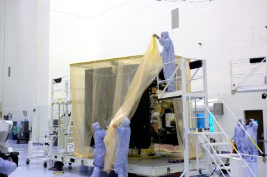 KENNEDY SPACE CENTER, FLA. - In a clean room inside the Payload Hazardous Servicing Facility (PHSF) at NASA?s Kennedy Space Center, Lockheed-Martin workers begin removing the protective cover from one of the boxes containing NASA?s Mars Reconnaissance Orbiter to a clean room. Here in the PHSF, the spacecraft will undergo multiple mechanical assembly operations and electrical tests to verify its readiness for launch. A test this month will verify the spacecraft?s ability to communicate through NASA's Deep Space Network tracking stations. A June test will check the deployment of the spacecraft's high gain communications antenna. Another major deployment test will check out the spacecraft's large solar arrays. The MRO was built by Lockheed-Martin for NASA?s Jet Propulsion Laboratory in California. It is the next major step in Mars exploration and scheduled for launch from Cape Canaveral Air Force Station in a window opening Aug. 10. The MRO is an important next step in fulfilling NASA?s vision of space exploration and ultimately sending human explorers to Mars and beyond.