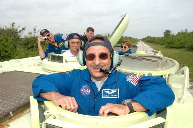 KENNEDY SPACE CENTER, FLA. - During Terminal Countdown Demonstration Test (TCDT) activities at NASA?s Kennedy Space Center, STS-114 Mission Specialist Charles Camarda is getting ready to practice driving an M-113, an armored personnel carrier that is used for speedy departure from the launch pad in an emergency. Behind him are Mission Specialist Stephen Robinson and Capt. George Hoggard, who is astronaut rescue team leader, and, at right, Commander Eileen Collins. The TCDT is held at KSC prior to each Space Shuttle flight. It provides the crew of each mission an opportunity to participate in simulated countdown activities. The test ends with a mock launch countdown culminating in a simulated main engine cutoff. The crew also spends time undergoing emergency egress training exercises at the launch pad. STS-114 is the first Return to Flight mission to the International Space Station. The launch window extends July 13 through July 31.