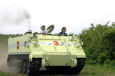 KENNEDY SPACE CENTER, FLA. - During Terminal Countdown Demonstration Test (TCDT) activities at NASA?s Kennedy Space Center, STS-114 Mission Specialist Stephen Robinson (right) practices driving an M-113, an armored personnel carrier that is used for speedy departure from the launch pad in an emergency. At left is Capt. George Hoggard, who is astronaut rescue team leader. The TCDT is held at KSC prior to each Space Shuttle flight. It provides the crew of each mission an opportunity to participate in simulated countdown activities. The test ends with a mock launch countdown culminating in a simulated main engine cutoff. The crew also spends time undergoing emergency egress training exercises at the launch pad. STS-114 is the first Return to Flight mission to the International Space Station. The launch window extends July 13 through July 31.