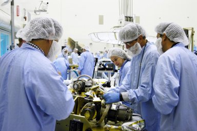 KENNEDY SPACE CENTER, FLA. - In the Payload Hazardous Servicing Facility at NASA?s Kennedy Space Center, engineers prepare a second gimbal for installation on a Mars Reconnaissance Orbiter (MRO) solar panel. A gimbal is an appliance that allows an object to remain horizontal even as its support tips. In the PHSF, the spacecraft will undergo multiple mechanical assembly operations and electrical tests to verify its readiness for launch. A major deployment test will check out the spacecraft?s large solar arrays. The MRO was built by Lockheed Martin for NASA?s Jet Propulsion Laboratory in California. It is the next major step in Mars exploration and scheduled for launch from Cape Canaveral Air Force Station in a window opening Aug. 10. The MRO is an important next step in fulfilling NASA?s vision of space exploration and ultimately sending human explorers to Mars and beyond.