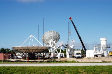 KENNEDY SPACE CENTER, FLA. - On June 14, work is underway on a radar site on North Merritt Island, Fla., constructing a C-band radar antenna (seen at left) and its base. The 50-foot C-band radar will be used for long-term Shuttle missions to track the launches and observe possible debris coming from the Shuttle. In the background (center) is an existing 30-foot C-band Pathfinder radar whose use was demonstrated on the Delta Messenger launch. It will be used on the upcoming two Return to Flight missions. The launch window for the first Return to Flight mission, STS-114, is July 13 to July 31.
