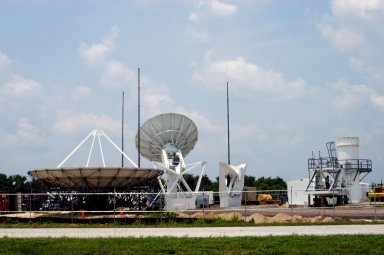 KENNEDY SPACE CENTER, FLA. - On June 16, work is underway on a radar site on North Merritt Island, Fla., constructing a C-band radar antenna (seen at left) and its base. The 50-foot C-band radar will be used for long-term Shuttle missions to track the launches and observe possible debris coming from the Shuttle. In the background (center) is an existing 30-foot C-band Pathfinder radar whose use was demonstrated on the Delta Messenger launch. It will be used on the upcoming two Return to Flight missions. The launch window for the first Return to Flight mission, STS-114, is July 13 to July 31.