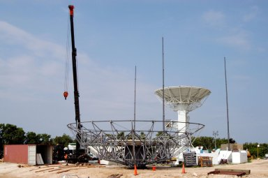 KENNEDY SPACE CENTER, FLA. - On May 27, a C-band radar antenna begins to be erected at a radar site on North Merritt Island, Fla. The 50-foot C-band radar will be used for long-term Shuttle missions to track the launches and observe possible debris coming from the Shuttle. In the background is an existing 30-foot C-band Pathfinder radar whose use was demonstrated on the Delta Messenger launch. It will be used on the upcoming two Return to Flight missions. The launch window for the first Return to Flight mission, STS-114, is July 13 to July 31.