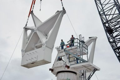 KENNEDY SPACE CENTER, FLA. - At a radar site on North Merritt Island, Fla., the second counterweight is being lifted for installation on the support structure (right) for a 50-foot C-band radar antenna dish. The radar will be used for Shuttle missions to track the launches and observe possible debris coming from the Shuttle. It will be used for the first time on STS-114. The launch window for the first Return to Flight mission is July 13 to July 31.