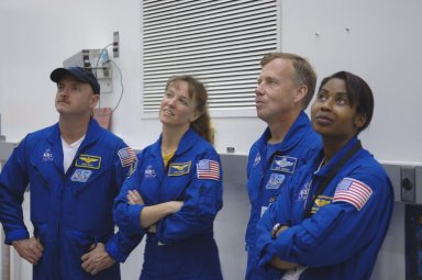 KENNEDY SPACE CENTER, FLA. - At Astrotech Space Operations in Titusville, Fla., STS-121 crew members look at equipment. From left are Pilot Mark Kelly, Mission Specialist Lisa Nowak, Mission Commander Steven Lindsey and Mission Specialist Stephanie Wilson. The STS-121 crew is at KSC to take part in Crew Equipment Interface Test activities, which provide hands-on experience with equipment they will use on-orbit. STS-121, the second Return to Flight mission, is targeted for launch in a lighted planning window of Sept. 9 to Sept. 25.