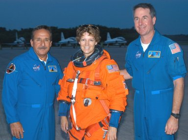 KENNEDY SPACE CENTER, FLA. - At the Shuttle Landing Facility on NASA Kennedy Space Center, STS-114 Mission Commander Eileen Collins pauses for a photo with fellow crew members. At left is Mission Specialist Charles Camarda; at right is Mission Specialist Stephen Robinson. Collins and Pilot James Kelly have been practicing night landings in the Shuttle Training Aircraft (STA) in preparation for the mission. The STA is a modified Grumman American Aviation-built Gulf Stream II executive jet that was modified to simulate an orbiter?s cockpit, motion and visual cues, and handling qualities. In flight, the STA duplicates the orbiter?s atmospheric descent trajectory from approximately 35,000 feet altitude to landing on a runway. Because the orbiter is unpowered during re-entry and landing, its high-speed glide must be perfectly executed the first time. Return to Flight Mission STS-114 is scheduled to launch aboard Space Shuttle Discovery with a crew of seven at 10:39 a.m. EDT on July 26. Landing is expected on Aug. 7.