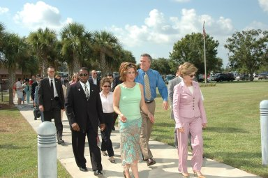 KENNEDY SPACE CENTER, FLA. - KSC Deputy Director Woodrow Whitlow Jr. (left) escorts distinguished guests to the VIP viewing site at NASA Kennedy Space Center. First Lady Laura Bush is in front (right) with Noelle Bush, the daughter of Florida Gov. Jeb Bush and Columba Bush behind her. They are attending the historic launch of Space Shuttle Discovery on Return to Flight mission STS-114, scheduled to lift off at 10:39 a.m. EDT from Launch Pad 39B with a crew of seven. Mrs. Bush is only the third First Lady to witness a Space Shuttle launch at KSC. On this mission to the International Space Station the crew will perform inspections on-orbit for the first time of all of the Reinforced Carbon-Carbon (RCC) panels on the leading edge of the wings and the Thermal Protection System tiles using the new Canadian-built Orbiter Boom Sensor System and the data from 176 impact and temperature sensors. Mission Specialists will also practice repair techniques on RCC and tile samples during a spacewalk in the payload bay. During two additional spacewalks, the crew will install the External Stowage Platform-2, equipped with spare part assemblies, and a replacement Control Moment Gyroscope contained in the Lightweight Multi-Purpose Experiment Support Structure. The 12-day mission is expected to end with touchdown at the Shuttle Landing Facility on Aug. 7.