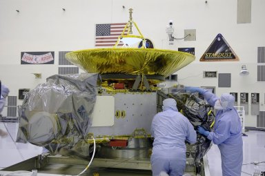"""KENNEDY SPACE CENTER, FLA. - In NASA Kennedy Space Center?s Payload Hazardous Servicing Facility, workers remove the protective cover around the New Horizons spacecraft. The spacecraft will be moved to a work stand for a checkout. New Horizons will make the first reconnaissance of Pluto and Charon - a """"double planet"""" and the last planet in our solar system to be visited by spacecraft. The mission will then visit one or more objects in the Kuiper Belt region beyond Neptune. New Horizons is scheduled to launch in January 2006, swing past Jupiter for a gravity boost and scientific studies in February or March 2007, and reach Pluto and its moon, Charon, in July 2015."""