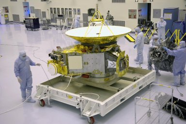 """KENNEDY SPACE CENTER, FLA. - In NASA Kennedy Space Center?s Payload Hazardous Servicing Facility, workers finish removing the protective cover around the New Horizons spacecraft. The spacecraft will be moved to a work stand for a checkout. New Horizons will make the first reconnaissance of Pluto and Charon - a """"double planet"""" and the last planet in our solar system to be visited by spacecraft. The mission will then visit one or more objects in the Kuiper Belt region beyond Neptune. New Horizons is scheduled to launch in January 2006, swing past Jupiter for a gravity boost and scientific studies in February or March 2007, and reach Pluto and its moon, Charon, in July 2015."""