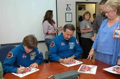 KENNEDY SPACE CENTER, FLA. - After speaking to the employees in the Space Station Processing Facility, STS-114 Mission Specialists Wendy Lawrence and Charles Camarda autograph crew photos. They and the other crew members visited several sites during their return to the Center. Their return is being celebrated at a gathering at the KSC Visitor Complex later this evening.