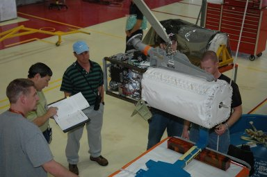 KENNEDY SPACE CENTER, FLA. - In NASA Kennedy Space Center?s Orbiter Processing Facility bay 3, a fuel cell removed from the orbiter Discovery is lowered toward a work stand. Fuel cells are located under the forward portion of the payload bay. They make power for the orbiter by mixing hydrogen and oxygen to produce electricity. Fuel cells also create potable water that is pumped into storage tanks for the crew to use in orbit. Discovery is the designated orbiter for the second return-to-flight mission, STS-121, scheduled for launch in May. Photo credit: NASA/Kim Shiflett