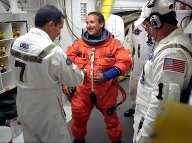 KENNEDY SPACE CENTER, FLA. - STS-114 Mission Specialist Charles Camarda is helped by the Closeout Crew with his launch and entry suit before entering Space Shuttle Discovery. This is Camarda?s first Shuttle flight. The Return to Flight mission to the International Space Station carries the External Stowage Platform-2, equipped with spare part assemblies, and a replacement Control Moment Gyroscope contained in the Lightweight Multi-Purpose Experiment Support Structure and Multi-Purpose Logistics Module Raffaello, housing 15 tons of hardware and supplies that will be transferred to the Station after the Shuttle docks to the complex . On this mission, the crew will perform inspections on-orbit for the first time of all of the Reinforced Carbon-Carbon (RCC) panels on the leading edge of the wings and the Thermal Protection System tiles using the new Canadian-built Orbiter Boom Sensor System and the data from 176 impact and temperature sensors. Mission Specialists will also practice repair techniques on RCC and tile samples during a spacewalk in the payload bay.