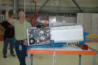 KENNEDY SPACE CENTER, FLA. - In NASA Kennedy Space Center?s Orbiter Processing Facility bay 3, the fuel cell removed from the orbiter Discovery is lowered onto a bracket on the work stand. Fuel cells are located under the forward portion of the payload bay. They make power for the orbiter by mixing hydrogen and oxygen to produce electricity. Fuel cells also create potable water that is pumped into storage tanks for the crew to use in orbit. Discovery is the designated orbiter for the second return-to-flight mission, STS-121, scheduled for launch in May. Photo credit: NASA/Kim Shiflett