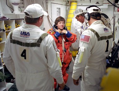 KENNEDY SPACE CENTER, FLA. - STS-114 Mission Specialist Wendy Lawrence is helped with her launch and entry suit by the Closeout Crew before entering Space Shuttle Discovery. The Return to Flight mission to the International Space Station carries the External Stowage Platform-2, equipped with spare part assemblies, and a replacement Control Moment Gyroscope contained in the Lightweight Multi-Purpose Experiment Support Structure and Multi-Purpose Logistics Module Raffaello, housing 15 tons of hardware and supplies that will be transferred to the Station after the Shuttle docks to the complex . On this mission, the crew will perform inspections on-orbit for the first time of all of the Reinforced Carbon-Carbon (RCC) panels on the leading edge of the wings and the Thermal Protection System tiles using the new Canadian-built Orbiter Boom Sensor System and the data from 176 impact and temperature sensors. Mission Specialists will also practice repair techniques on RCC and tile samples during a spacewalk in the payload bay.