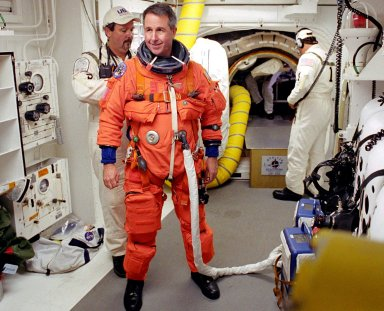 KENNEDY SPACE CENTER, FLA. - STS-114 Mission Specialist Stephen Robinson is helped by the Closeout Crew with his launch and entry suit before entering Space Shuttle Discovery. The Return to Flight mission to the International Space Station carries the External Stowage Platform-2, equipped with spare part assemblies, and a replacement Control Moment Gyroscope contained in the Lightweight Multi-Purpose Experiment Support Structure and Multi-Purpose Logistics Module Raffaello, housing 15 tons of hardware and supplies that will be transferred to the Station after the Shuttle docks to the complex . On this mission, the crew will perform inspections on-orbit for the first time of all of the Reinforced Carbon-Carbon (RCC) panels on the leading edge of the wings and the Thermal Protection System tiles using the new Canadian-built Orbiter Boom Sensor System and the data from 176 impact and temperature sensors. Mission Specialists will also practice repair techniques on RCC and tile samples during a spacewalk in the payload bay.