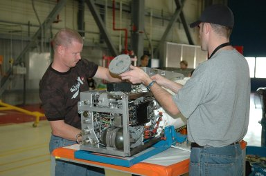 KENNEDY SPACE CENTER, FLA. - In NASA Kennedy Space Center?s Orbiter Processing Facility bay 3, technicians begin dismantling the fuel cell removed from the orbiter Discovery. Fuel cells are located under the forward portion of the payload bay. They make power for the orbiter by mixing hydrogen and oxygen to produce electricity. Fuel cells also create potable water that is pumped into storage tanks for the crew to use in orbit. Discovery is the designated orbiter for the second return-to-flight mission, STS-121, scheduled for launch in May. Photo credit: NASA/Kim Shiflett