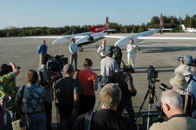 KENNEDY SPACE CENTER, FLA. - After the landing of the Virgin Atlantic Airways GlobalFlyer aircraft at NASA Kennedy Space Center?s Shuttle Landing Facility, Center Director James Kennedy (center, in front of the plane) addresses the media. At right is the pilot, Steve Fossett. At left are Jim Ball, KSC Spaceport Development manager, and Winston Scott, executive director of Florida Space Authority. The aircraft is being relocated from Salina, Kan., to the Shuttle Landing Facility to begin preparations for an attempt to set a new world record for the longest flight made by any aircraft. An exact takeoff date for the record-setting flight has not been determined and is contingent on weather and jet-stream conditions. The window for the attempt opens in mid-January, making the flight possible anytime between then and the end of February. NASA agreed to let Virgin Atlantic Airways use Kennedy's Shuttle Landing Facility as a takeoff site. The facility use is part of a pilot program to expand runway access for non-NASA activities.