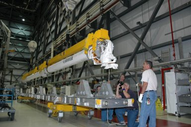 KENNEDY SPACE CENTER, FLA. - In the Orbiter Processing Facility bay 1 at NASA Kennedy Space Center, the remote manipulator system, or boom, is lifted off a stand via overhead cranes. The boom will be installed in Atlantis? payload bay. Atlantis is the designated orbiter for mission STS-115, the 19th assembly flight to the International Space Station. The payload includes the P3/P4 solar arrays. The launch planning window has not been determined yet for STS-115.