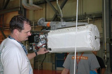 KENNEDY SPACE CENTER, FLA. - In NASA Kennedy Space Center?s Orbiter Processing Facility bay 3, technicians remove a piece of hardware from the side of a fuel cell removed from the orbiter Discovery. Fuel cells are located under the forward portion of the payload bay. They make power for the orbiter by mixing hydrogen and oxygen to produce electricity. Fuel cells also create potable water that is pumped into storage tanks for the crew to use in orbit. Discovery is the designated orbiter for the second return-to-flight mission, STS-121, scheduled for launch in May. Photo credit: NASA/Kim Shiflett