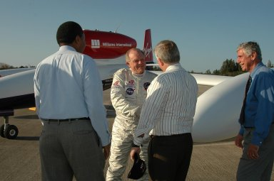KENNEDY SPACE CENTER, FLA. - After landing the Virgin Atlantic Airways GlobalFlyer aircraft at NASA Kennedy Space Center?s Shuttle Landing Facility, pilot Steve Fossett is greeted by Center Director James Kennedy (center) and Executive Director of Florida Space Authority Winston Scott. At far right is Jim Ball, KSC Spaceport Development manager. The aircraft is being relocated from Salina, Kan., to the Shuttle Landing Facility to begin preparations for an attempt to set a new world record for the longest flight made by any aircraft. An exact takeoff date for the record-setting flight has not been determined and is contingent on weather and jet-stream conditions. The window for the attempt opens in mid-January, making the flight possible anytime between then and the end of February. NASA agreed to let Virgin Atlantic Airways use Kennedy's Shuttle Landing Facility as a takeoff site. The facility use is part of a pilot program to expand runway access for non-NASA activities.