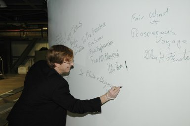 KENNEDY SPACE CENTER, FLA. - In the Vertical Integration Facility on Launch Complex 41, Cape Canaveral Air Force Station, Hal Weaver, New Horizons project scientist with the Johns Hopkins University Applied Physics Laboratory, signs the fairing enclosing the New Horizons spacecraft. The fairing protects the spacecraft during launch and flight through the atmosphere. Once out of the atmosphere, the fairing is jettisoned. The compact 1,060-pound New Horizons probe carries seven scientific instruments that will characterize the global geology and geomorphology of Pluto and its moon Charon, map their surface compositions and temperatures, and examine Pluto's complex atmosphere. New Horizons is the first mission in NASA's New Frontiers program of medium-class planetary missions. The spacecraft, designed for NASA by the Johns Hopkins University Applied Physics Laboratory in Laurel, Md., will fly by Pluto and Charon as early as summer 2015.