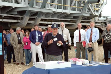KENNEDY SPACE CENTER, FLA. - On the occasion of the 40th anniversary of the crawler transporter used for moving space shuttles to the NASA Kennedy Space Center?s launch pads, former crawler engineer Bill Clemens talks to the media and invited guests (behind him) Rick Drollinger (blue shirt), whose father Richard was director of engineering at Marion Power Shovel Co. in Ohio where the crawlers were initially built in 1965; Philip Koehring Jr. (on right), whose father was project manager at Marion; and Koehring?s sons Doug and John. Media representatives and invited guests had the opportunity to tour one of NASA's two crawlers. This included the driver cab and engine room. Guests included current drivers and operators, as well as drivers from the Apollo Program. In January 1966, the crawler completed its first successful move with a 10.6-million-pound launch umbilical tower. It moved three-quarters of a mile in about nine hours. Throughout 40 years of service, the two crawlers have moved more than 3,500 miles and carried seven vehicles.