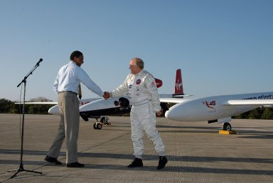 KENNEDY SPACE CENTER, FLA. - After the landing of the Virgin Atlantic Airways GlobalFlyer aircraft at NASA Kennedy Space Center?s Shuttle Landing Facility, Winston Scott (left), executive director of Florida Space Authority, brings pilot Steve Fossett to the microphone for a few words to the media. The aircraft is being relocated from Salina, Kan., to the Shuttle Landing Facility to begin preparations for an attempt to set a new world record for the longest flight made by any aircraft. An exact takeoff date for the record-setting flight has not been determined and is contingent on weather and jet-stream conditions. The window for the attempt opens in mid-January, making the flight possible anytime between then and the end of February. NASA agreed to let Virgin Atlantic Airways use Kennedy's Shuttle Landing Facility as a takeoff site. The facility use is part of a pilot program to expand runway access for non-NASA activities.