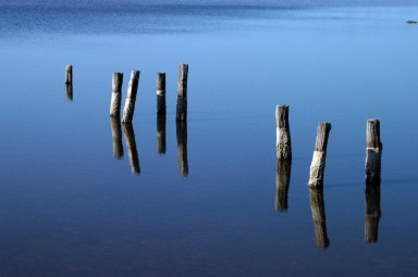 KENNEDY SPACE CENTER, FLA. - The remnant pilings of a long-gone dock appear to float in air due to their reflection in the blue, still water of a pond near NASA Kennedy Space Center. The area is north of the Launch Complex 39 Area and art of the Merritt Island National Wildlife Refuge, which shares a boundary with the center. The wildlife refuge is a habitat for more than 310 species of birds, 25 mammals, 117 fishes and 65 amphibians and reptiles. In addition, the Refuge supports 19 endangered or threatened wildlife species on Federal or State lists, more than any other single refuge in the U.S.
