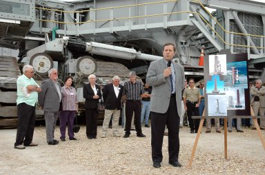 KENNEDY SPACE CENTER, FLA. - Standing in front of one of the crawler transporters at NASA Kennedy Space Center, Director of Space Shuttle Processing Mike Wetmore addresses invited guests (behind him) and the media on the occasion of the 40th anniversary of the crawler transporters. Media representatives and invited guests had the opportunity to tour one of NASA's two crawlers. This included the driver cab and engine room. Guests included current drivers and operators, as well as drivers from the Apollo Program. In January 1966, the crawler completed its first successful move with a 10.6-million-pound launch umbilical tower. It moved three-quarters of a mile in about nine hours. Throughout 40 years of service, the two crawlers have moved more than 3,500 miles and carried seven vehicles.