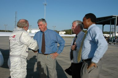 KENNEDY SPACE CENTER, FLA. - After landing the Virgin Atlantic Airways GlobalFlyer aircraft at NASA Kennedy Space Center?s Shuttle Landing Facility, pilot Steve Fossett is welcomed (left to right) by KSC Spaceport Development Manager Jim Ball, Center Director James Kennedy and Executive Director of Florida Space Authority Winston Scott. The aircraft is being relocated from Salina, Kan., to the Shuttle Landing Facility to begin preparations for an attempt to set a new world record for the longest flight made by any aircraft. An exact takeoff date for the record-setting flight has not been determined and is contingent on weather and jet-stream conditions. The window for the attempt opens in mid-January, making the flight possible anytime between then and the end of February. NASA agreed to let Virgin Atlantic Airways use Kennedy's Shuttle Landing Facility as a takeoff site. The facility use is part of a pilot program to expand runway access for non-NASA activities.