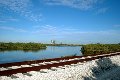 KENNEDY SPACE CENTER, FLA. - Railroad tracks run along the shoreline east of Launch Pads 39A and 39B, seen in the background. North of Launch Pad 39B, the tracks turn west, passing the KSC Shuttle Landing Facility and heading through the Merritt Island National Wildlife Refuge until joining the East Coast Railway north of Titusville, Fla.