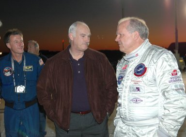 KENNEDY SPACE CENTER, FLA. - As a rosy dawn creeps over the horizon, Deputy Associate Administrator for Exploration Operations Michael Foale (left) and astronaut Bill Readdy (center) talk to Steve Fossett about the anticipated flight of the Virgin Atlantic GlobalFlyer. Fossett will pilot the GlobalFlyer on a record-breaking attempt by flying solo, non-stop without refueling, to surpass the current record for the longest flight of any aircraft. Fossett is expected to take off from the KSC SLF. Later, takeoff of the GlobalFlyer was postponed due to a fuel leak that appeared during the last moments of loading. The next planned takeoff attempt is 7 a.m. Feb. 8 from the SLF. Photo credit: NASA/Kim Shiflett