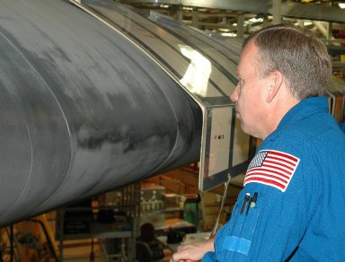 KENNEDY SPACE CENTER, FLA. - Inside the Orbiter Processing Facility bay 3 at NASA's Kennedy Space Center, STS-121 Commander Steven Lindsey gets a close look at the wing leading edge of Discovery, the launch vehicle for the mission. He and other crew members -- Pilot Mark Kelly and Mission Specialists Lisa Nowak, Stephanie Wilson, Michael Fossum and Piers Sellers -- are at Kennedy for a crew equipment interface test, which provides hands-on experience with equipment they will use on orbit. Launch of STS-121, the second return-to-flight mission, is scheduled for no earlier than May. Photo credit: NASA/Kim Shiflett