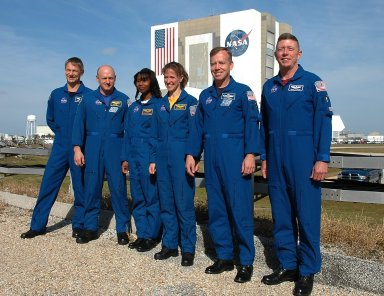 KENNEDY SPACE CENTER, FLA. - The STS-121 crew stands for a photo in front of the Vehicle Assembly Building after a media conference. From left are Mission Specialist Piers Sellers, Pilot Mark Kelly, Mission Specialists Stephanie Wilson and Lisa Nowak, Commander Steven Lindsey and Mission Specialist Michael Fossum. The remaining member of the crew, not pictured, is Mission Specialist Thomas Reiter. The crew is at NASA Kennedy Space Center for the crew equipment interface test, which provides hands-on experiences with equipment used on-orbit. The launch of STS-121, the second return-to-flight mission, is scheduled for May. Photo credit: NASA/Kim Shiflett