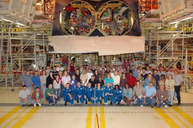 KENNEDY SPACE CENTER, FLA. - Inside the Orbiter Processing Facility bay 3 at NASA's Kennedy Space Center, the STS-121 crew kneels for a photo with the vehicle crew. The crew members, recognized by the blue flight suits, are (left to right) Mission Specialists Piers Sellers and Michael Fossum, Commander Steven Lindsey, Mission Specialist Lisa Nowak, Pilot Mark Kelly and Mission Specialist Stephanie Wilson. The crew is at Kennedy for the crew equipment interface test, which provides hands-on experience with equipment they will use on orbit.