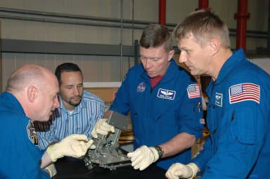 KENNEDY SPACE CENTER, FLA. - In NASA Kennedy Space Center's Orbiter Processing Facility bay 3, members of the STS-121 crew practice working with hardware for the mission under the watchful eyes of Tomas Gonzalez-Torres, with NASA's Johnson Space Center. At left is Pilot Mark Kelly; at right are Mission Specialists Michael Fossum and Piers Sellers. The crew is at Kennedy to take part in the crew equipment interface test, which provides hands-on experience with equipment to be used on-orbit. Launch of Space Shuttle Discovery on mission STS-121, the second return-to-flight mission, is scheduled no earlier than May.