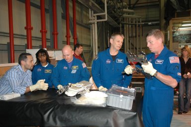 KENNEDY SPACE CENTER, FLA. - In NASA Kennedy Space Center's Orbiter Processing Facility bay 3, members of the STS-121 crew practice working with equipment for the mission. Starting from left are Tomas Gonzalez-Torres, with NASA's Johnson Space Center; Mission Specialist Stephanie Wilson, Pilot Mark Kelly, and Mission Specialists Piers Sellers and Michael Fossum. The crew is at Kennedy to take part in the crew equipment interface test, which provides hands-on experience with equipment to be used on-orbit. Launch of Space Shuttle Discovery on mission STS-121, the second return-to-flight mission, is scheduled no earlier than May.