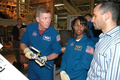 KENNEDY SPACE CENTER, FLA. - In NASA Kennedy Space Center's Orbiter Processing Facility bay 3, STS-121 Mission Specialist Michael Fossum (left) talks to Tomas Gonzalez-Torres, with NASA's Johnson Space Center, about the equipment he is handling. Next to Fossum is Mission Specialist Stephanie Wilson. The crew is at Kennedy to take part in the crew equipment interface test, which provides hands-on experience with equipment to be used on-orbit. Launch of Space Shuttle Discovery on mission STS-121, the second return-to-flight mission, is scheduled no earlier than May.