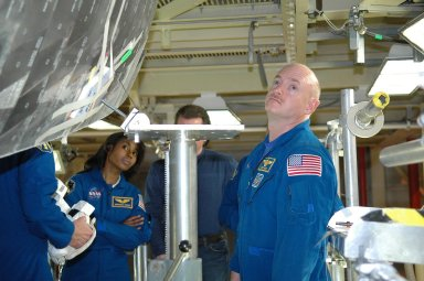 KENNEDY SPACE CENTER, FLA. - Inside the Orbiter Processing Facility bay 3 at NASA's Kennedy Space Center, members of the STS-121 crew take a close look at Discovery, the launch vehicle for the mission. Seen are Mission Specialist Stephanie Wilson and Pilot Mark Kelly. The crew is at Kennedy for the crew equipment interface test, which provides hands-on experience with equipment they will use on orbit. Launch of STS-121, the second return-to-flight mission, is scheduled for no earlier than May. Photo credit: NASA/Kim Shiflett