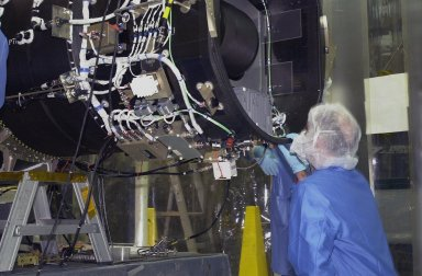 KENNEDY SPACE CENTER, FLA. - Inside Orbital Sciences? Building 1555 at Vandenberg Air Force Base in California, a worker examines the end of the Pegasus XL launch vehicle that will be mated with the Space Technology 5 (ST5) spacecraft. The ST5 contains three microsatellites with miniaturized redundant components and technologies. Each will validate New Millennium Program selected technologies, such as the Cold Gas Micro-Thruster and X-Band Transponder Communication System. After deployment from the Pegasus, the micro-satellites will be positioned in a ?string of pearls? constellation that demonstrates the ability to position them to perform simultaneous multi-point measurements of the magnetic field using highly sensitive magnetometers. The data will help scientists understand and map the intensity and direction of the Earth?s magnetic field, its relation to space weather events, and affects on our planet. With such missions, NASA hopes to improve scientists? ability to accurately forecast space weather and minimize its harmful effects on space- and ground-based systems. Launch of ST5 is scheduled no earlier than March 6 from Vandenberg Air Force Base.